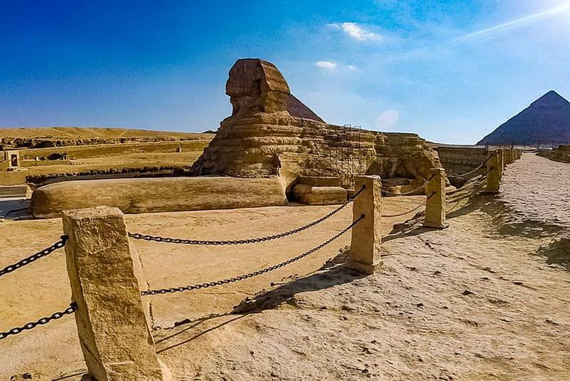 Великий Сфинкс Гизы — древнейшая грандиозная монолитная статуя. Но ни точный возраст, ни его строители не известны. По мнению ученых, он построен египтянами Древнего царства во время правления фараона Хафрена в XXVI веке до нашей эры. Однако несколько свидетельств указывают на то, что Сфинкс намного старше и построен кем-то, кроме египтян. В 1857 году Огюст Мариетт, основатель египетского музея в Каире, преуспел в переводе надписей на обелиске, высеченном из известняковой глыбы в VII века до нашей эры. В нем подробно рассказывается о том, как фараон Хеопс наткнулся на Сфинкса, который в то время был погребенным в песке в течение тысяч лет, а Хеопс только раскопал и восстановил памятник. Профессор и геолог Бостонского университета доктор Роберт Шох проанализировал Сфинкса и пришел к выводу, что модели выветривания на его поверхности были не результатом ветра, а следствием сильных ливней. В соседних пирамидах нет таких признаков эрозии, но они были построены примерно в тот же период, что и Сфинкс. Это заставило некоторых поверить, что статуя присутствовала в районе задолго до 2500 г. до н.э., так как эти места испытывали засуху в течение последних 5000 лет. Существует теория, что Нил соответствует Млечному Пути, а Великие Пирамиды положению звезд в созвездии Ориона. Согласно ей, массивная скульптура Сфинкса ориентирована на созвездие Льва, и появилась она в 10 500 году до нашей эры. Действительно, в то время плато Гиза получало гораздо больше осадков, чем 4500 лет назад. Роберт Шох полагает, что фараон Хафрен просто восстановил Сфинкса, чтобы включить его в свой погребальный комплекс. По мнению профессора, нынешняя голова не могла быть оригинальной, потому что ее эрозия не совпадает с разрушениями остальной части статуи. Если египтяне не строили Сфинкса, то кто это сделал, и что с ними случилось? Тайна вокруг него углубляется. По словам мистика Эдгара Кейси, это были атланты. Под колоссальным строением они возвели секретную комнату под названием Зал Летописи, в которо